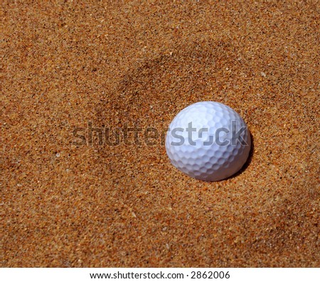 Bunkered - golf ball with a poached egg lie in a bunker  (main focus on the ball and the surrounding sand) - stock photo