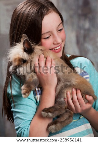 Bunny Love.  Attractive young girl holding a fluffy bunny.