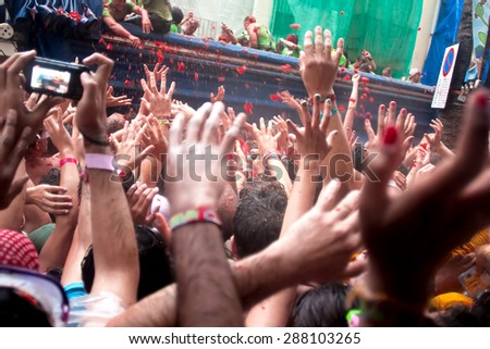 BUNOL, SPAIN - AUGUST 28: With a truck throw tomatoes into crowd on Tomatina festival in Bunol, August 28, 2013 in Spain - stock photo