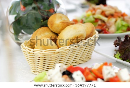 Buns, festive table setting. Buns in a wicker basket. Banquet table, Serving dishes, Food restaurant. Wedding evening. A range of snacks. Decor with white tablecloth.  - stock photo