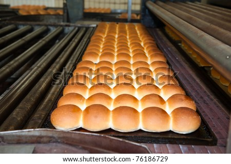 buns of bread being made in a factory - stock photo