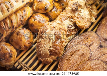 Buns of puff pastry on shelves of French bakery - stock photo