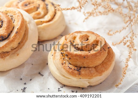 Buns with poppy seeds on bakery paper lying on white barn painted wooden table with flowers, macro close-up - stock photo