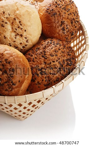 Buns with sesame in a woven basket on a white background