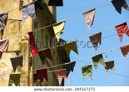Bunting, colorful party flags against old building - stock photo