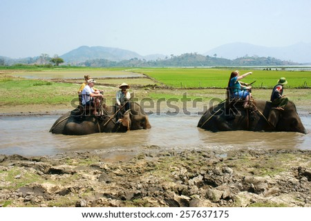 BUON ME THUOT, VIET NAM- FEB 25: Group of tourist traveling Vietnamese countryside, traveler ride elephant, cross rural with green flield, this is Daklak's travel product, Vietnam, Feb 25, 2015