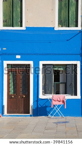 Burano island in lagoon of Venice; famous brightly-colored houses - stock photo