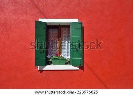 Burano island, Venice. Decorated window on the red wall. Colorful houses island and landmark of Veneto region, Italy - stock photo