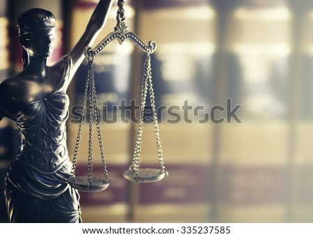 Burden of proof - Moodily lit legal law concept image with Scales of justice backlit and row of law books in background.  Hazy light from right good for text copy. - stock photo