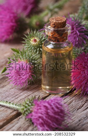 burdock oil in a glass bottle on the table macro vertical  - stock photo