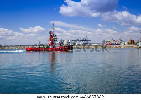 Burgas - July 9: A little red boat - leader sail into port amid cranes, warehouses and administrative buildings on July 9, 2016 Bourgas, Bulgaria