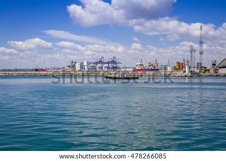 Burgas - July 9: Port - small boat, cranes, warehouses, wharf, silos, bird against the blue sky with white clouds on July 9, 2016, Burgas, Bulgaria