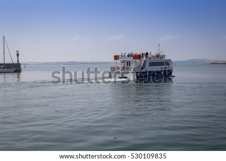 "Burgas - July 29: Small tourist pleasure craft ""Anastasia"" set sail from the port along the lighthouse against the blue sky with white clouds on July 29, 2016, Burgas, Bulgaria"