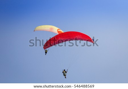 Burgas - July 29: Two paraglider - red and yellow flying against the blue sky on July 29, 2016, Burgas, Bulgaria