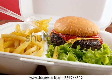 Burger and fries portion in takeout food box with plastic fork , closeup - stock photo