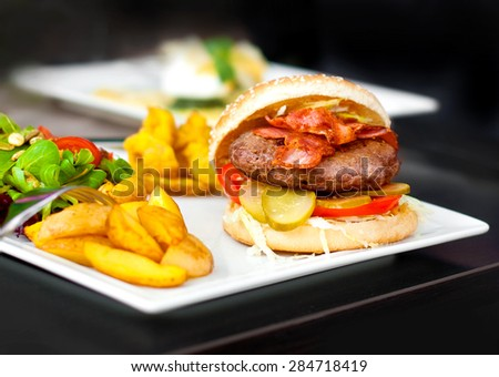 Burger. Beef, cheese, tomatoes, onion, cucumber, lettuce cabbage salad and french fries - stock photo