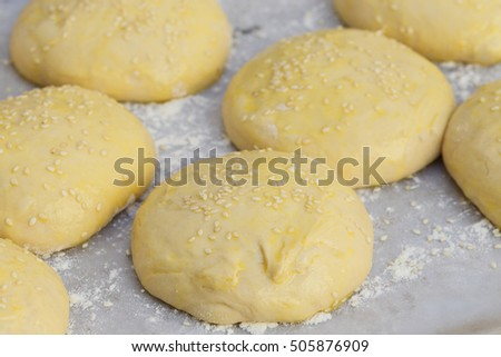 Burger-bun dough or batter ready for the oven, sprinkled with sesame seeds
