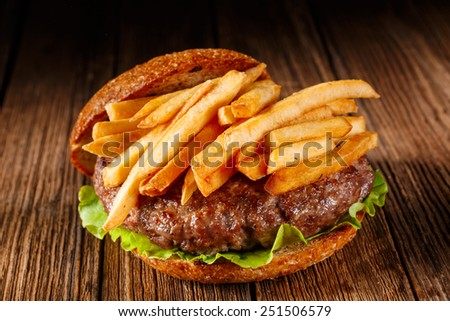 Burger. Burger on wooden background. Vintage burger. Home made burger. Fastfood meal. Pub burger. American style burger. Delicious burger. Gourmet burger. Burger on wooden table. French fries.