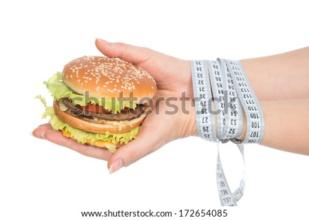 Burger cheeseburger in hands with measure tape isolated on white background. Healthy weight loss diet concept.