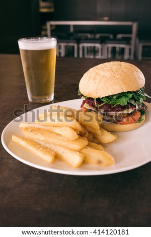 burger, chips and a beer, there's beetroot on the burger, you must be in Australia - stock photo
