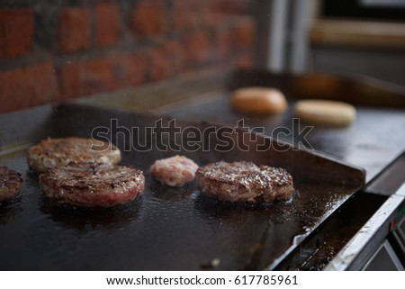 Burger cooking in restaurant kitchen.Fresh bbq meat roasting on pan.American fast food cookery.Big fat piece of meat fry in oil.Unhealthy eating,high cholesterol level food
