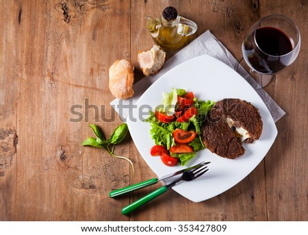 Burger cutlet stuffed with cheese inside of legumes with vegetable salad, a glass of red wine and fresh bread served on a plate. on a wooden table. - stock photo