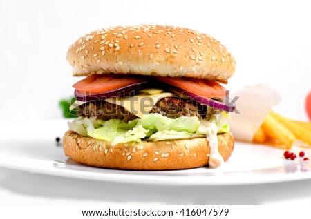 Burger full face with vegetables, spices and fries. Meat hamburger. Beef hamburger. Organic hamburger - stock photo