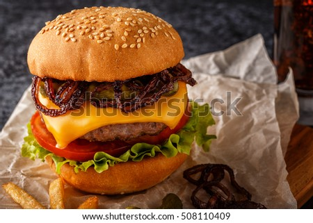 Burger, hamburger with french fries and fresh vegetables on a dark  background.