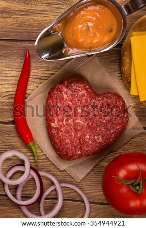 Burger ingredients over rustic wooden table. Top view. Toned image - stock photo