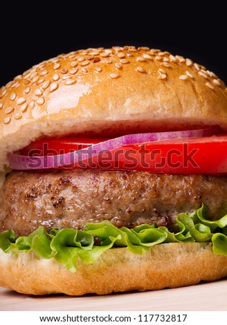 Burger isolated on black background. Fast food meal.