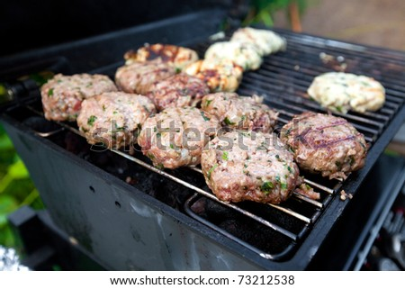 Burger meat patties on an outdoor grill for barbecue - stock photo