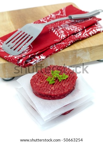 Burger patties isolated on a chopping board - stock photo