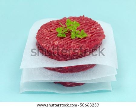 Burger patties isolated on a pale blue background - stock photo