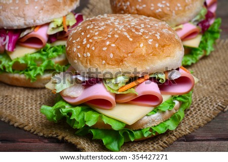 Burger sandwich with sausage, cheese and vegetables on a wooden background. - stock photo