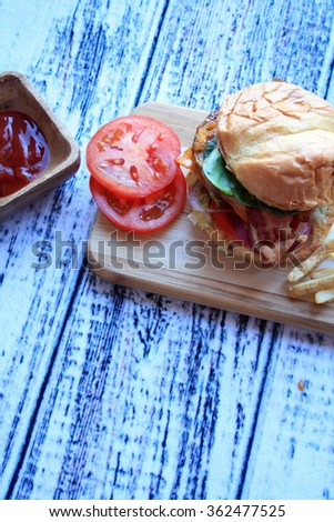 burger tomato cheddar cheese french fries red onion ketchup in wooden bowl on a cutting board on a wooden background/hamburger fries ketchup/vertical burger and fries - stock photo