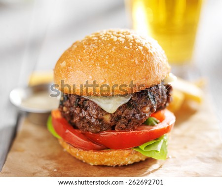 burger with beer and fries served on wax paper - stock photo