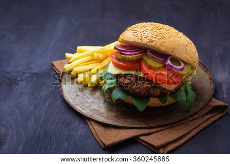 Burger with cutlet, tomato, cheese and french fries. Selective focus - stock photo