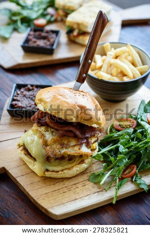 Burger with egg, cheese and bacon, served with salad, fries and relish. - stock photo
