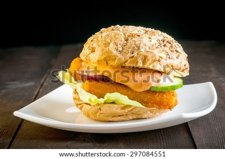 Burger with fish sticks on a white plate - stock photo