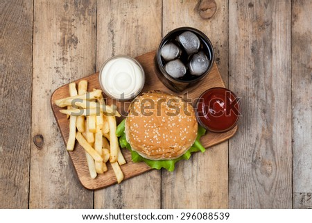 burger with french fries on wooden background - stock photo