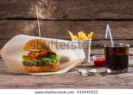 Burger with fries and cola. Beverage and hamburger on stick. Delicious fast food with drink. New dishes worth tasting. - stock photo