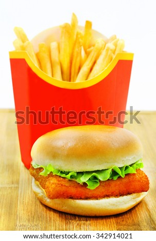 Burger with fries and fish is photographed close-up on a wooden board