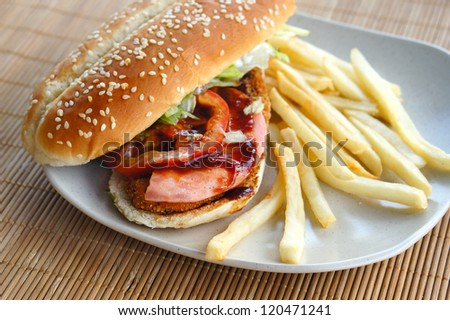 Burger with fries on bamboo mat - stock photo