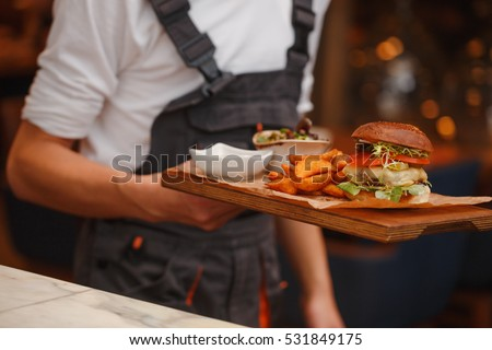 Burger with fries on waiters hands