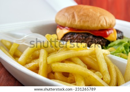 Burger with fries portion from fast food service closeup - stock photo