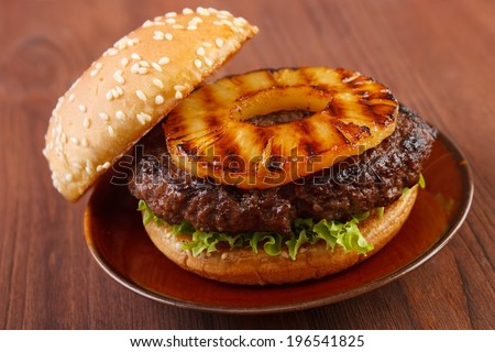 Burger with grilled pineapple on dish - stock photo