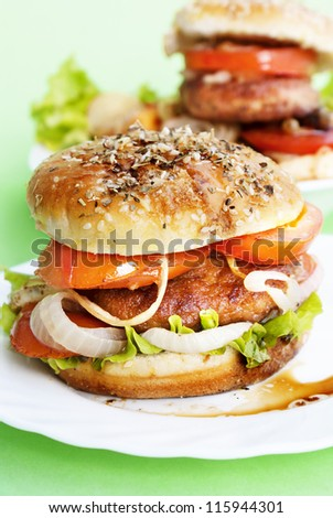 Burger with meat and baked vegetables on a light green background - stock photo