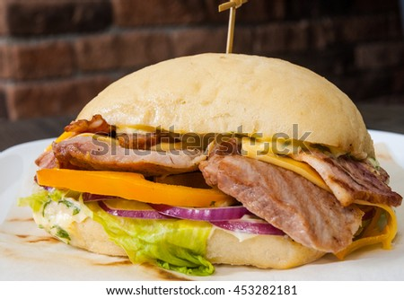 burger with meat, tomato, onion, cheese, lettuce on plate - stock photo
