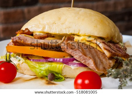 burger with meat, tomato, onion, cheese, lettuce on plate against the background of a brick wall
