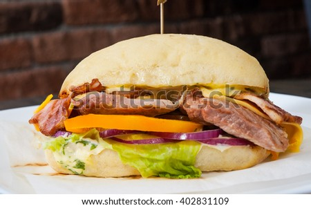 burger with meat, tomato, onion, cheese, lettuce on wooden table